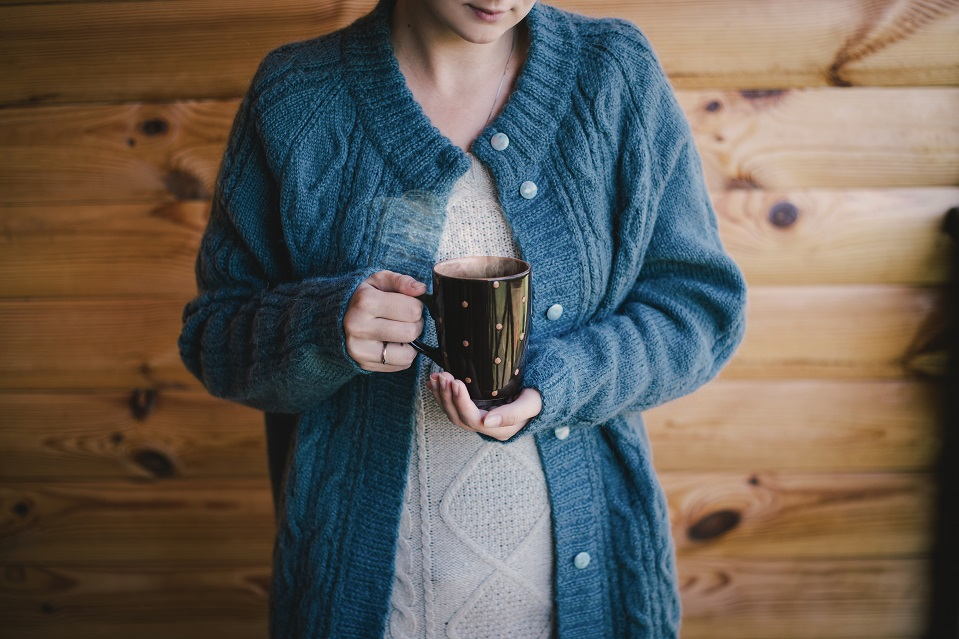 woman in a woolen sweater witn a cup of hot tea